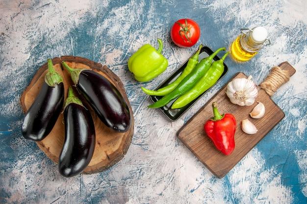 Bovenaanzicht aubergines op boom houten bord hete pepers op zwarte plaat op snijplank aubergine olie op blauw-witte achtergrond