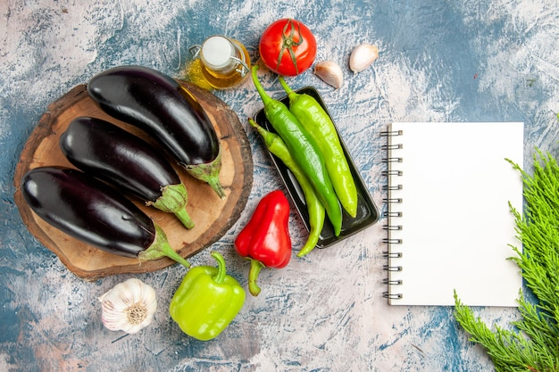 Bovenaanzicht aubergines op boom houten bord met hete pepers op zwarte plaat