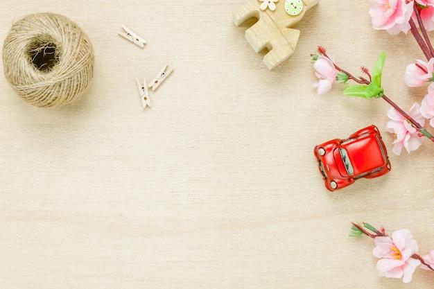 Bovenaanzicht auto huis touw en bloem op houten achtergrond.