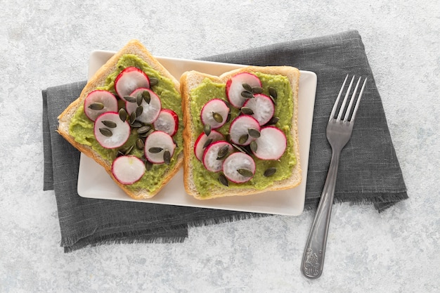 Bovenaanzicht avocado toast met radijs en zaden op plaat met vork