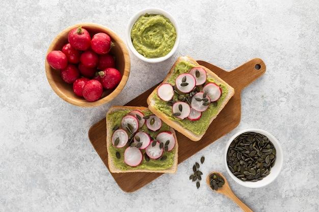 Bovenaanzicht avocado toast met radijs en zaden op snijplank
