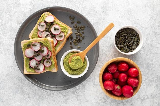 Bovenaanzicht avocadotoost met radijs en zaden