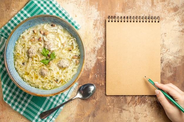Bovenaanzicht azerbeidzjaanse erishte in kom op keukenhanddoek een groene pen in vrouwenhand een notitieboekje op beige achtergrond