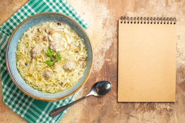 Bovenaanzicht azerbeidzjaanse erishte in kom op keukenhanddoek een lepel een notitieboekje op beige achtergrond