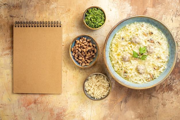 Bovenaanzicht azerbeidzjaanse erishte in kom verschillende voeders in kommen een notitieboekje op beige achtergrond