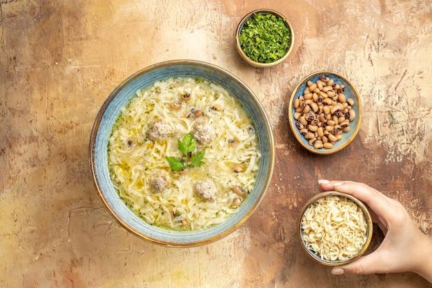 Bovenaanzicht azerbeidzjaanse erishte in kom verschillende voeders in vrouw hand in kommen op beige achtergrond