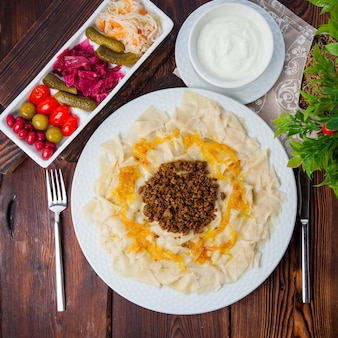 Bovenaanzicht azerbeidzjaanse goeroe khingal kaukasische pasta met gebakken gehakt vlees en ui met zure roomsaus en augurken horizontaal