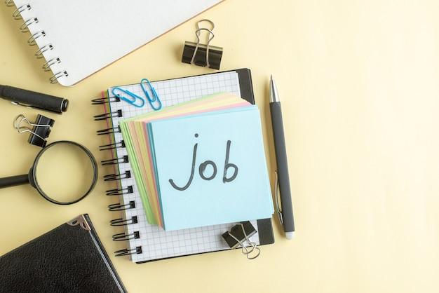 Bovenaanzicht baan geschreven notitie samen met kleurrijke kleine aantekeningen op papier op lichte achtergrond school kantoor baan kladblok kleur werk