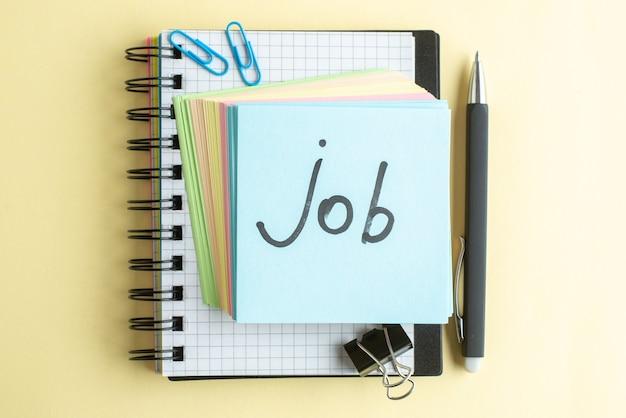 Bovenaanzicht baan geschreven notitie samen met kleurrijke kleine aantekeningen op papier op lichte achtergrond school kantoor werk schrift baan kladblok kleur