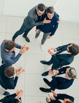 Bovenaanzicht. baas en zakelijk team feliciteren met de beste werknemer. concept van succes