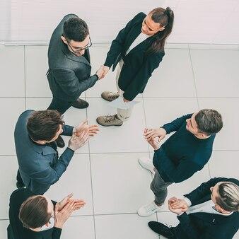 Bovenaanzicht. baas handen schudden met een jonge werknemer. het begrip succes.