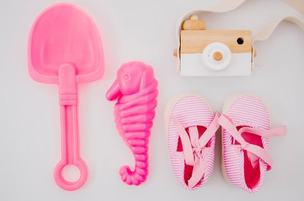 Bovenaanzicht baby schoenen met roze speelgoed