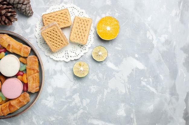 Bovenaanzicht bagels en macarons met wafels op wit