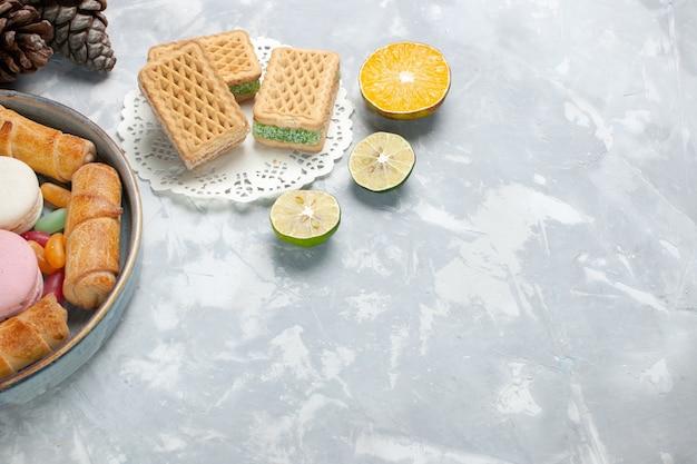 Bovenaanzicht bagels en wafels met citroen op wit
