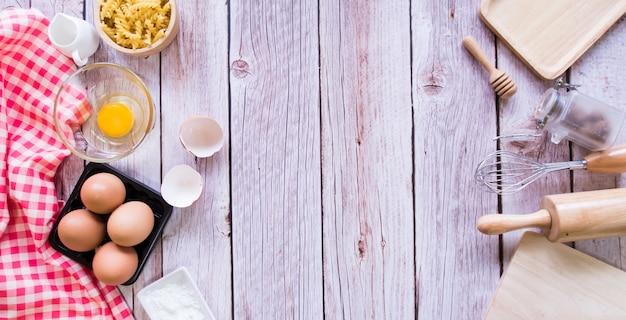 Bovenaanzicht, bakken apparatuur en ingrediënt op houten tafel.