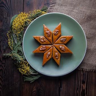 Bovenaanzicht baklava met mimosa bloemen in ronde plaat