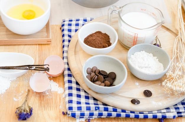 Bovenaanzicht bakvoorbereiding op houten tafel, bakken ingrediënten. kom, eieren en bloem, deegroller en eierschalen op een houten bord, bakconcept