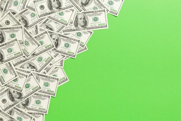 Bovenaanzicht bankbiljetten op gekleurd bureau met copyspace op de top. honderd-dollarbiljetten met stapel geld in het midden. bovenaanzicht van het bedrijfsleven