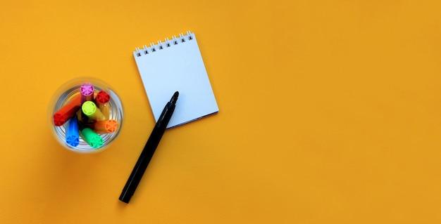 Bovenaanzicht banner van viltstiften en lege kladblok op geel