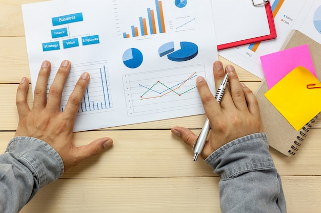 Bovenaanzicht bedrijfspersoon die grafieken en grafieken op de achtergrond van de bureaublad bespreekt.