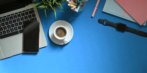 Bovenaanzicht beeld van computer laptop zetten kleurrijke bureau met koffiekopje, potplant, potloden in glazen vaas, smartphone, notitie, smartwatch en notebook. ordelijk werkruimte concept.