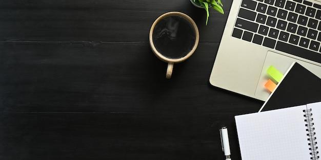 Bovenaanzicht beeld van computer laptop zetten zwarte bureau en omgeven door notebook, dagboek, potplant, koffiekopje en pen. ordelijk werkruimte concept.