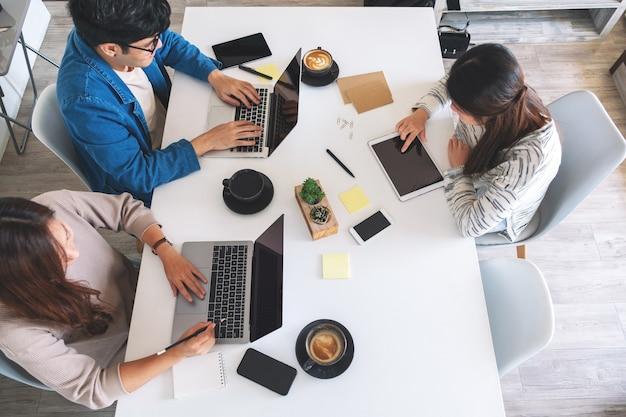 Bovenaanzicht beeld van mensen die laptopcomputer en tablet-pc gebruiken en werken op de tafel op kantoor
