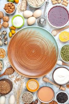 Bovenaanzicht beige ronde bord kommen met tarwekorrels sesamzaad pompoenpitten walnoten eieren cumcuats