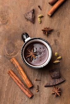 Bovenaanzicht beker met warme chocolademelk en kaneel op tafel
