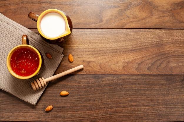 Bovenaanzicht bekers met melk en honing op de tafel