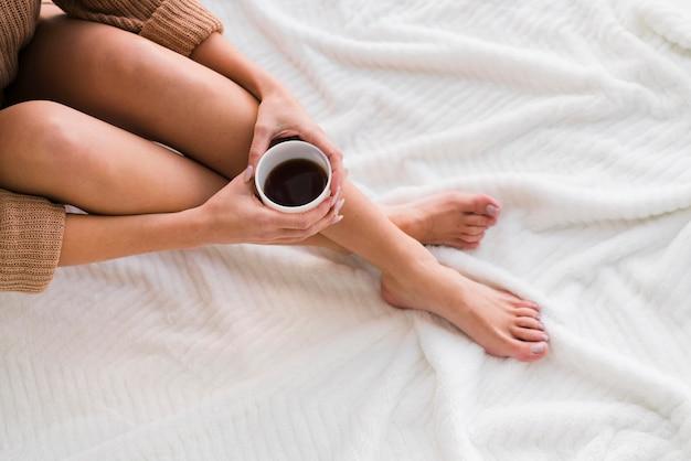Bovenaanzicht benen en mok koffie