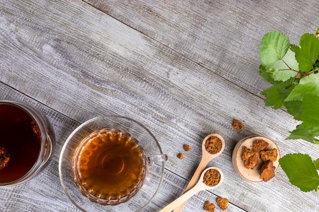 Bovenaanzicht berk paddestoel chaga drank in glazen beker en chaga stukken op diagonale houten tafel met kopie ruimte.