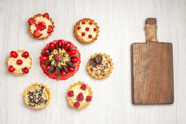 Bovenaanzicht berry cake op de rode ovale kanten kleedje taartjes en een houten snijplank op de witte houten grond