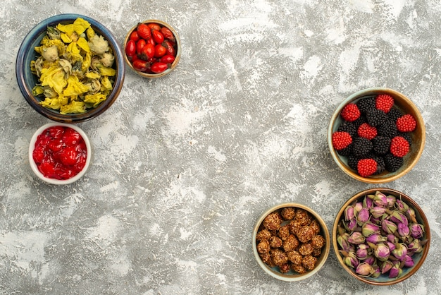 Bovenaanzicht berry confitures met noten en gedroogde bloemen op witte achtergrond confiture candy tea sweet