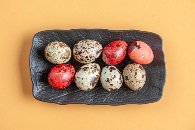 Bovenaanzicht beschilderde eieren binnen plaat op geel oppervlak vakantie lente kleurrijk sierlijk concept novruz etnische