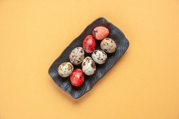 Bovenaanzicht beschilderde eieren in plaat op geel oppervlak vakantie lente kleurrijk sierlijk concept etnisch