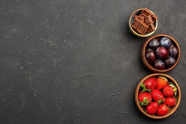 Bovenaanzicht bessen en snoep houten kommen chocolade aardbeien en bessen op de donkere tafel