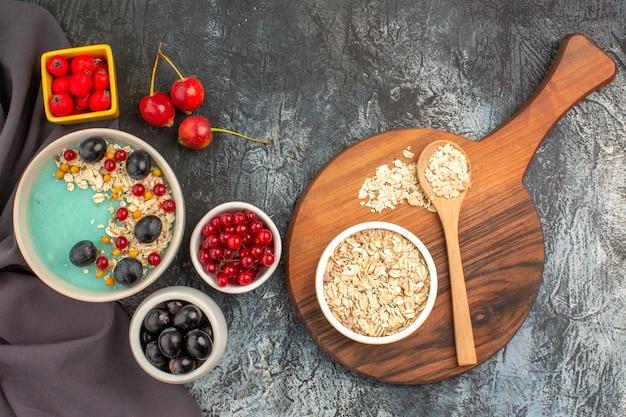 Bovenaanzicht bessen kleurrijke bessen granaatappel zaden op het tafellaken havermout op het bord
