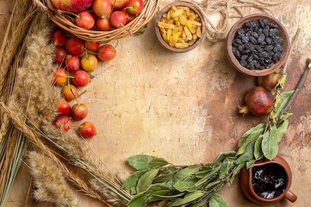 Bovenaanzicht bessen mandje appels bessen rozijnen in kommen chocoladesaus granaatappels