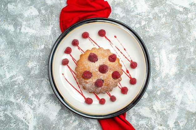Bovenaanzicht bessencake op witte ovale plaat rode sjaal op grijze ondergrond