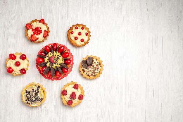 Bovenaanzicht bessentaart links boven op het rode ovale kanten kleedje en verschillende taartjes op de witte houten ondergrond