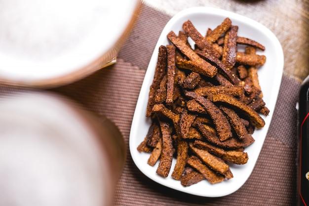 Bovenaanzicht bier snack crackers gemaakt van bruin brood op een bord