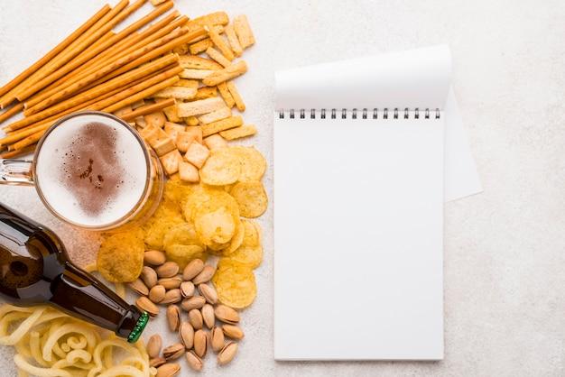 Bovenaanzicht bier, snacks en notitieboekje