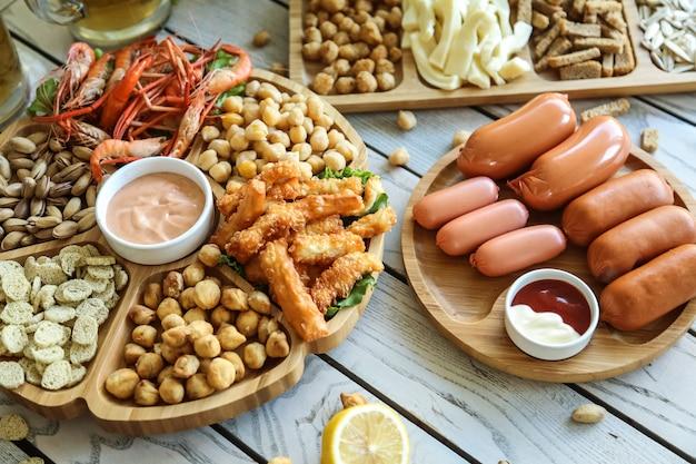 Bovenaanzicht bier snacks worstjes met gebakken erwten pistachenoten croutons garnalen met kaas en sauzen op stands