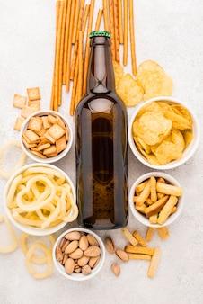 Bovenaanzicht bierfles en snacks