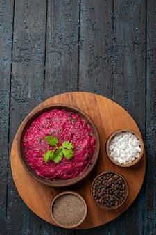 Bovenaanzicht bietensalade met kruiden op donker bureau