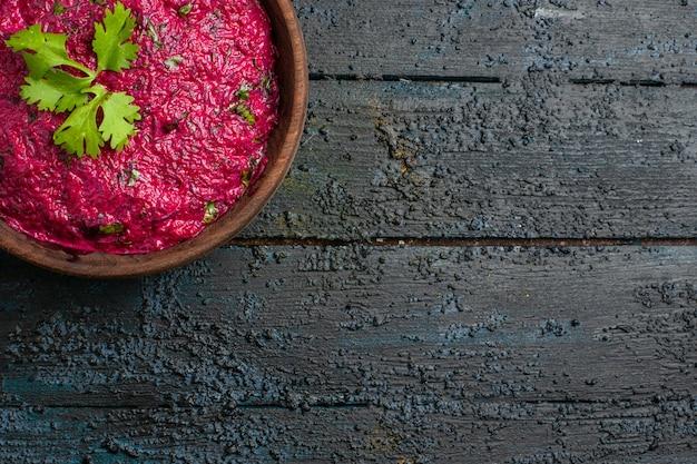 Bovenaanzicht bietensalade met walnoten en mayyonaise op donker bureau