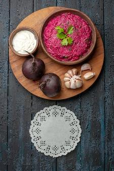 Bovenaanzicht bietensalade met zure room en knoflook op donker bureau