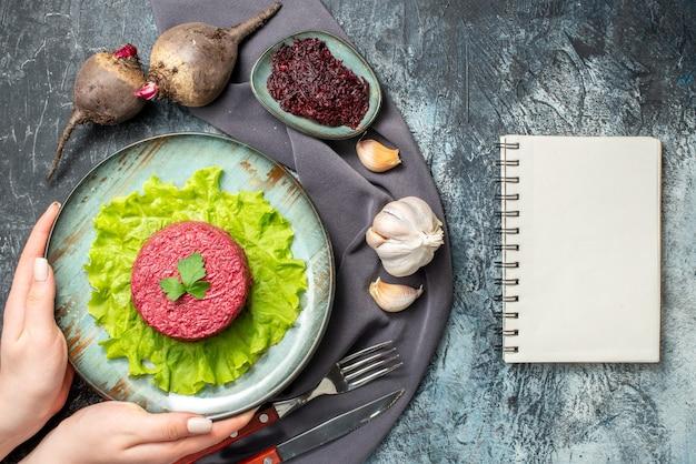 Bovenaanzicht bietensalade op bord in handen van de vrouw knoflookbieten geraspte biet in kleine kom vork en mes paarse sjaal kladblok op grijze tafel