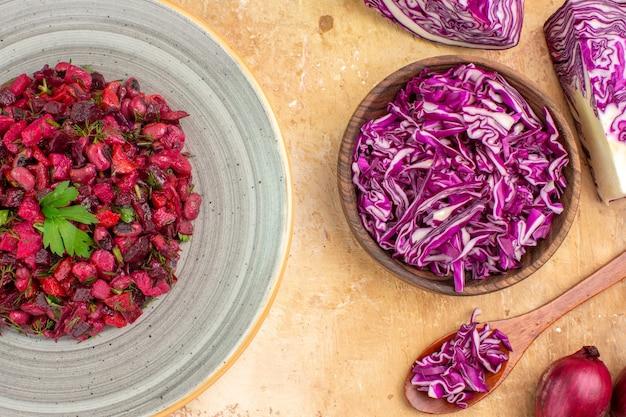 Bovenaanzicht bietensalade op een bord met rode uien en gehakte rode kool in een kom op een houten tafel